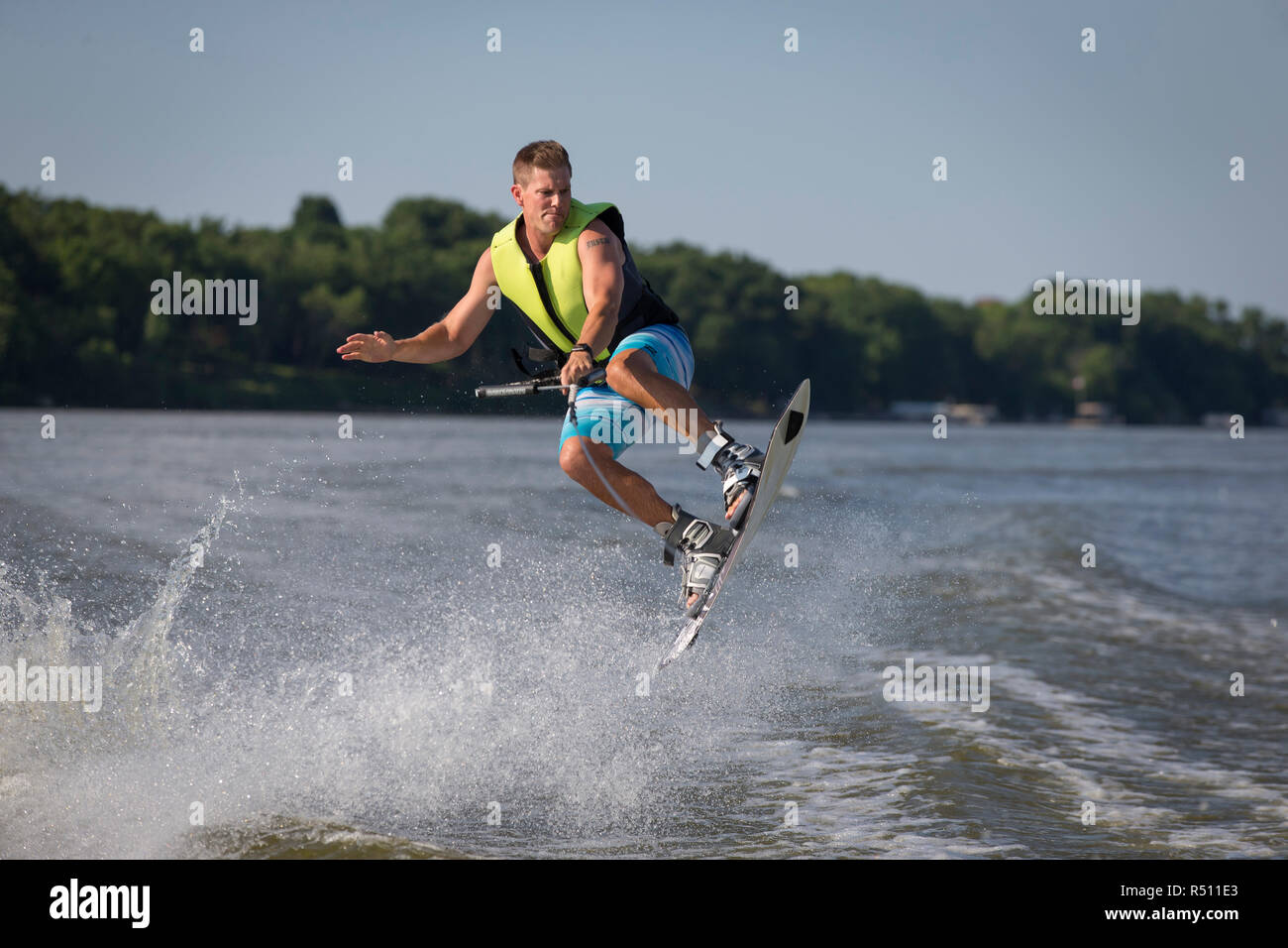 Photograph of man in mid-air while wakeboarding on river - Stock Image