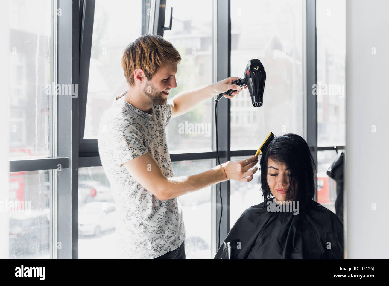 Smiling woman getting haircut by handsome hairdresser - Stock Image