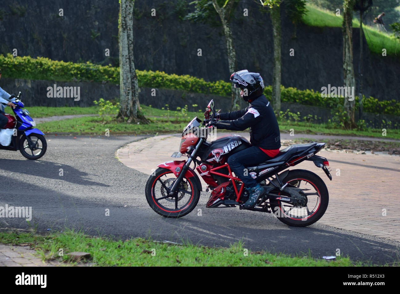 BEKASI, WEST JAVA, INDONESIA. DESEMBER 1, 2018 : Unrecognized people, riders with black red motorcycles use helmet. editorial use only - Stock Image