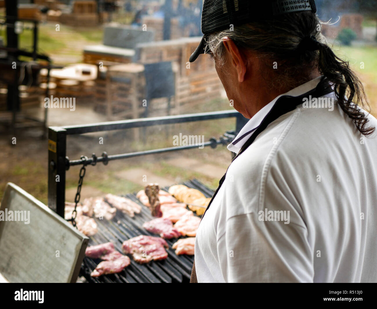 back of an old man with a pony tail making a barbecue for a party the meat is still raw - Stock Image