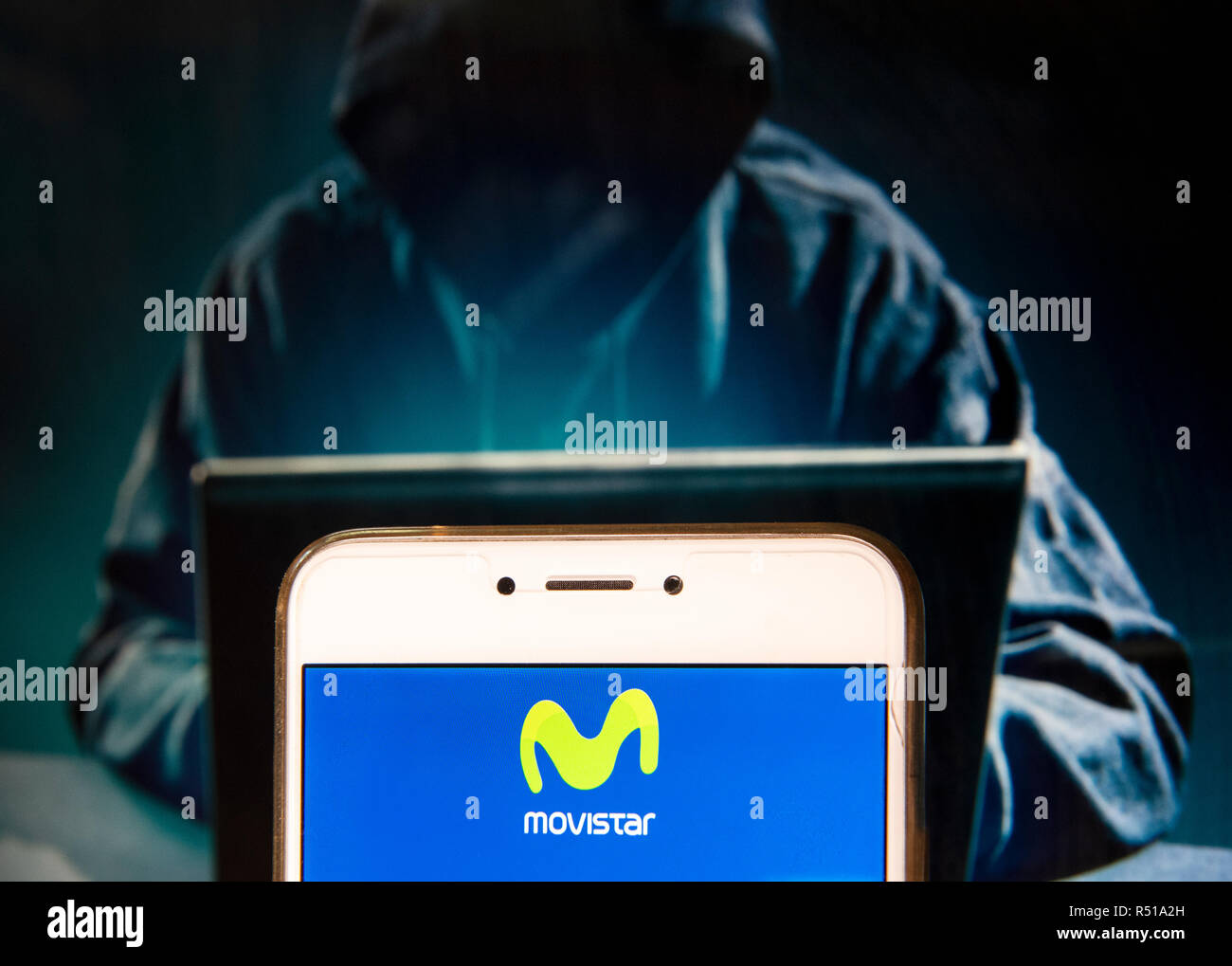 Spanish telecommunications brand owned by Telefonica and largest mobile phone operator, Movistar, logo is seen on an Android mobile device with a figure of hacker in the background. - Stock Image