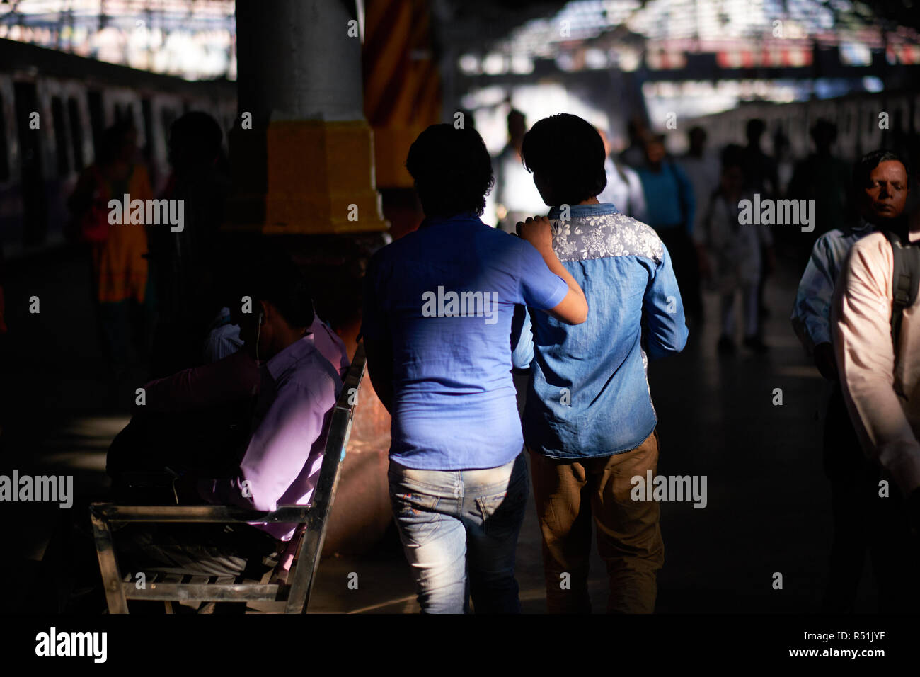 Two close friends on a platform at Chhatrapati Shivaji Maharaj Terminus (CSMT), the busiest rail station in Mumbai, India, and a UNESCO heritage site - Stock Image