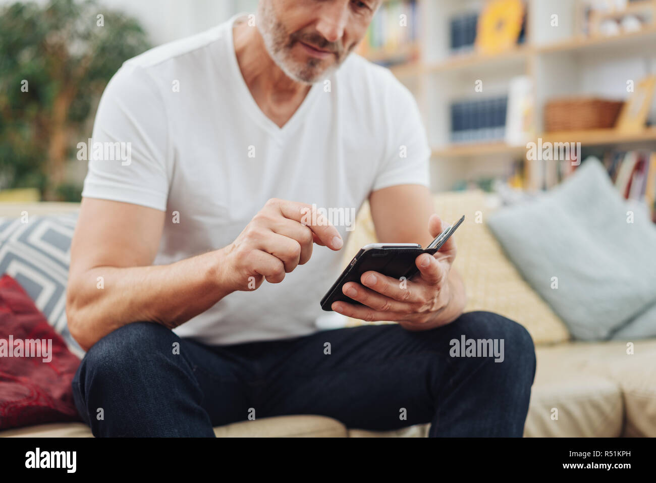 Older man dialing out a call on his mobile phone as he relaxes on a sofa at home in a closeup cropped view - Stock Image