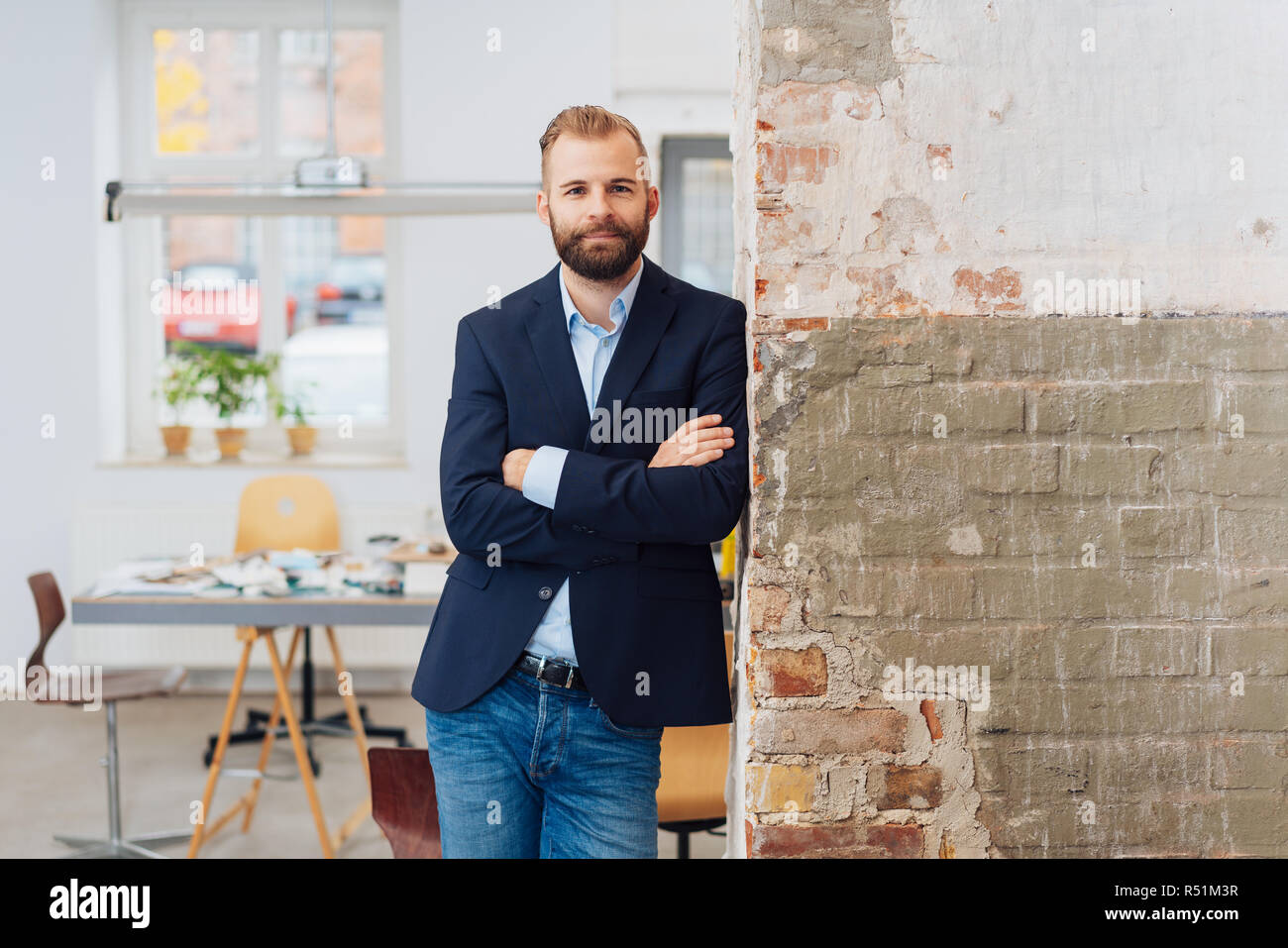 A young, entrepreneurial man looking at the camera while leaning on a wall at home. - Stock Image