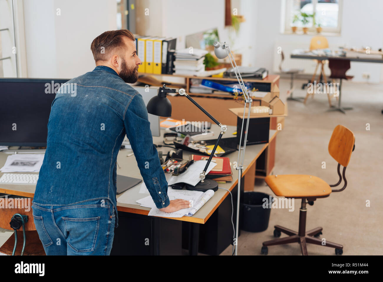 An entrepreneurial young man working from a messy desk in a home office. - Stock Image