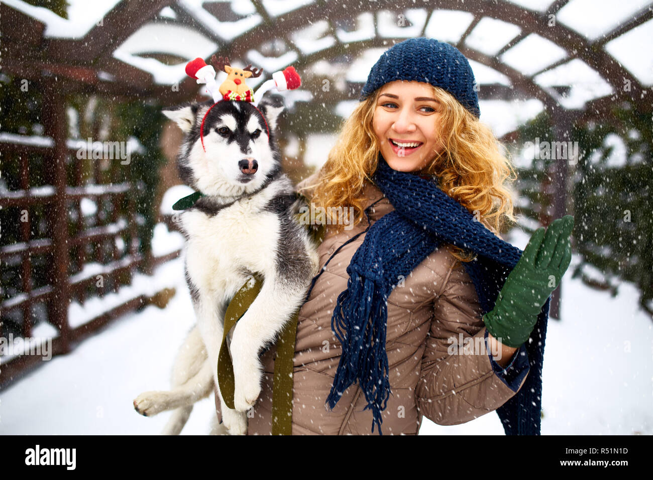 Attractive authentic caucasian woman hugs funny malamute dog wearing santa dear christmas antlers. Curly smiling female having fun with huskie puppy on new year. Pet is best gift for holidays. - Stock Image