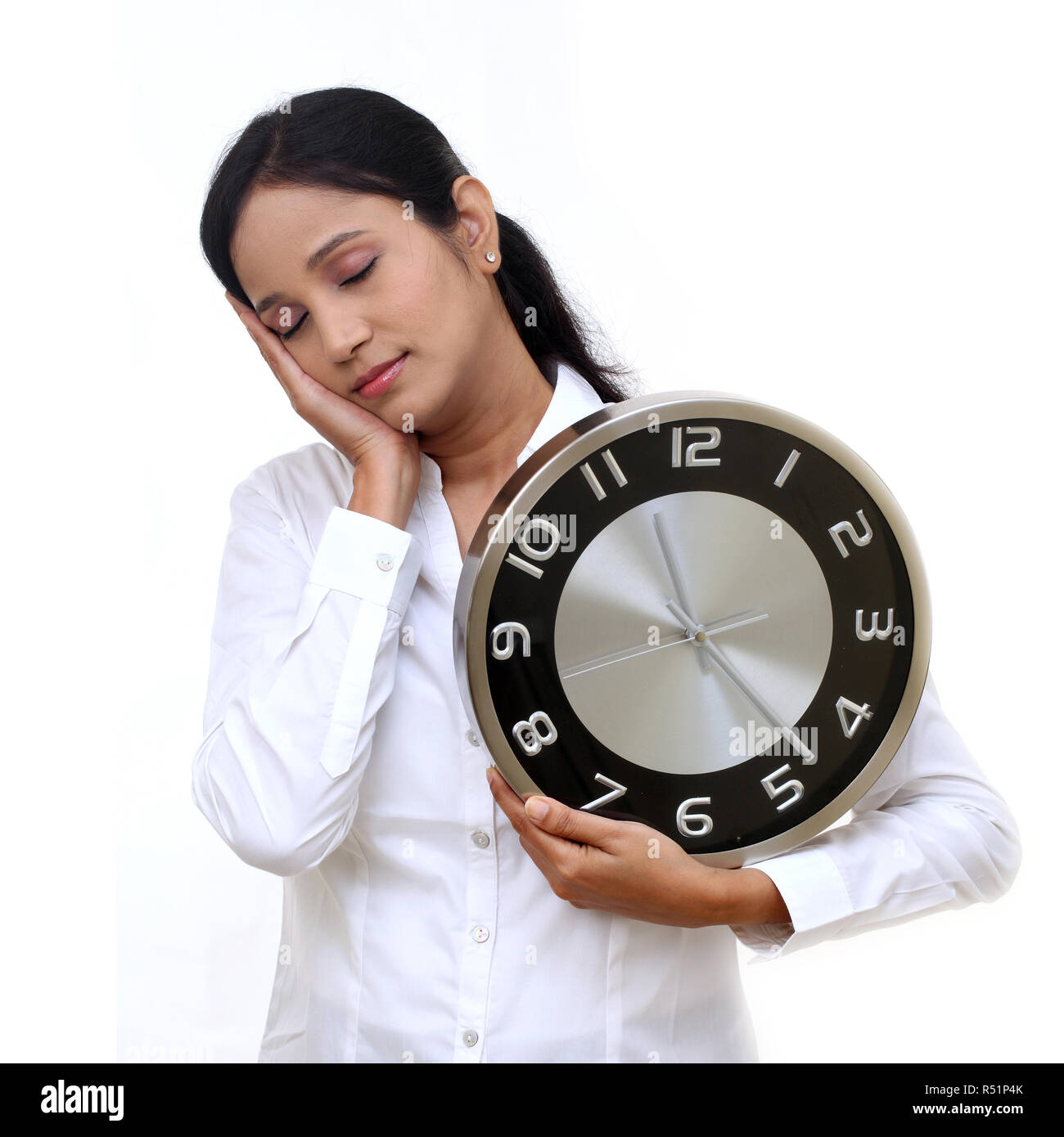 Stressful young business woman holding clock in her hand - Stock Image