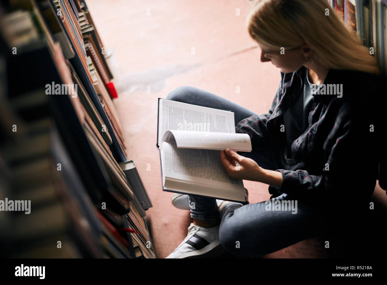 Young girl sitting on the floor in traditional library at bookshelves, reading books. Smiling and laughing student working with laptop, studying. Higher education. Student life - Stock Image