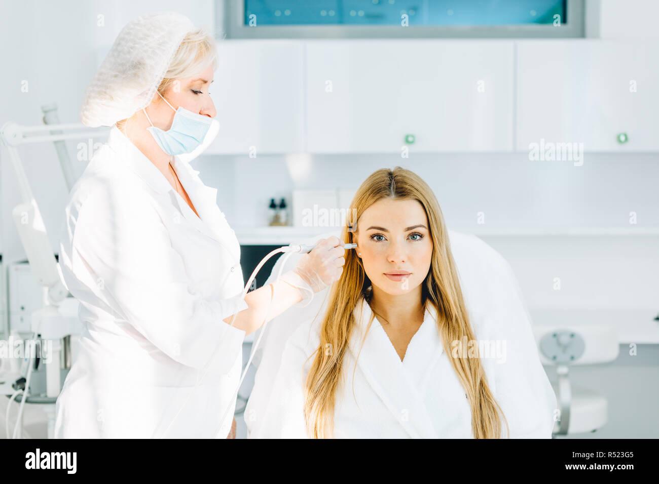 Blonde woman undergoes a procedure of facial gas-liquid oxygen peeling - Stock Image
