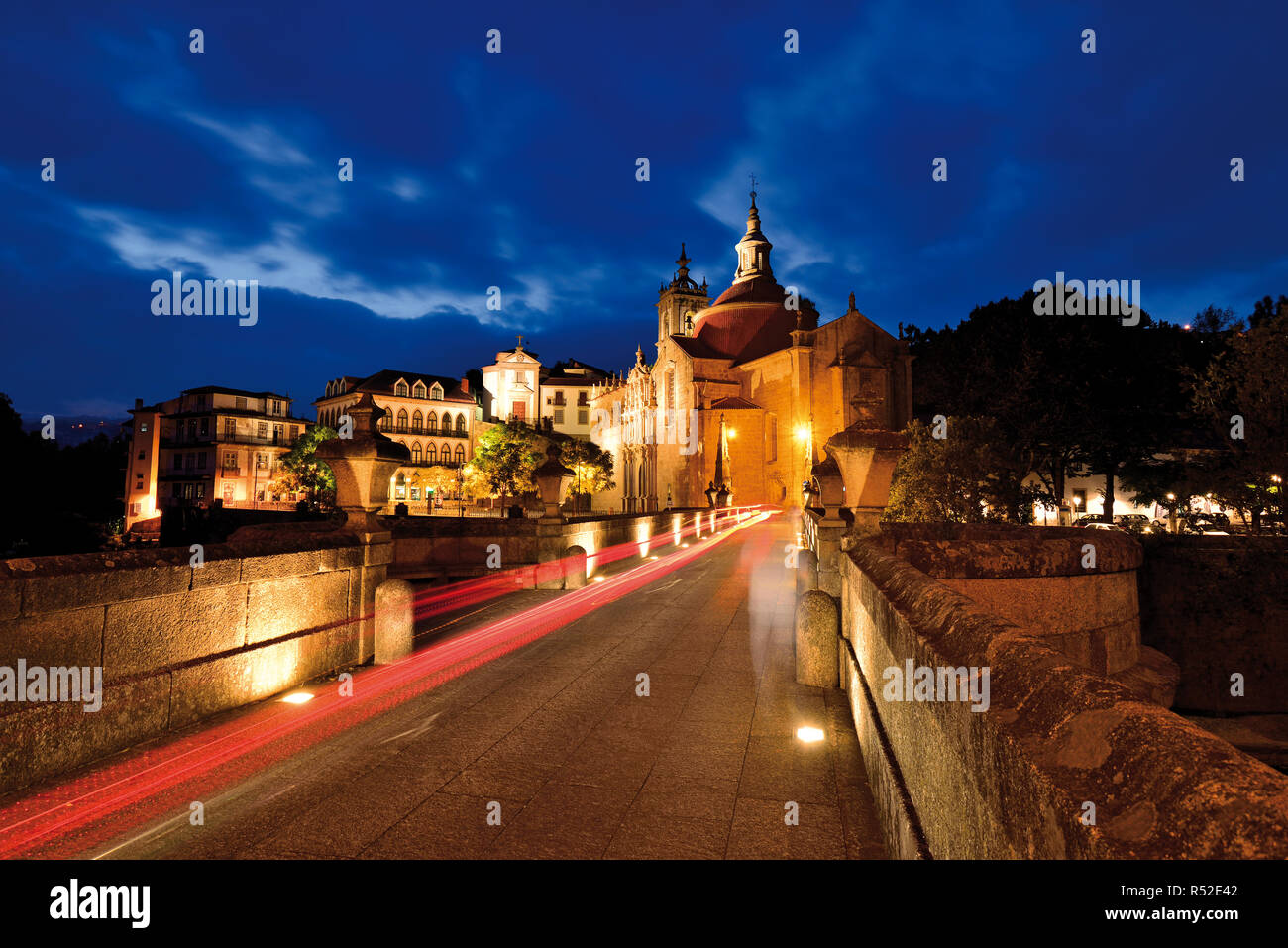 Nocturnal illuminated medieval bridge and convent at  blue hour - Stock Image