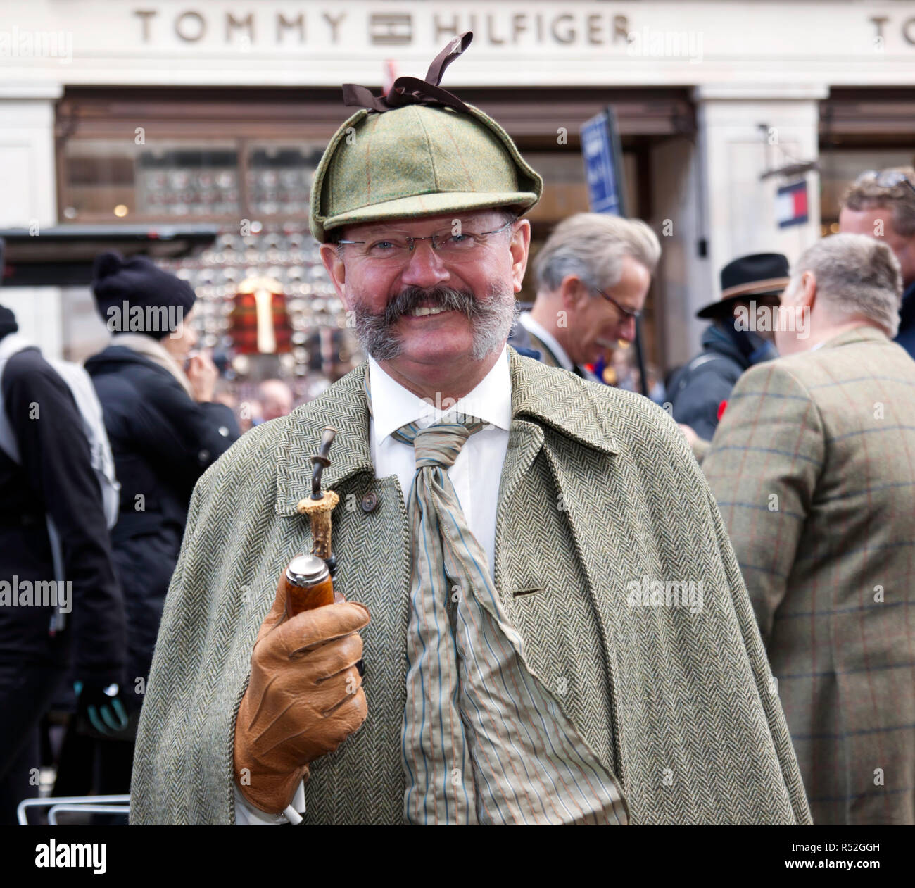 A smiling man in period costume poses near his vehicle, in the Veteran Car Zone of the 2018 Regents Street Motor Show Stock Photo