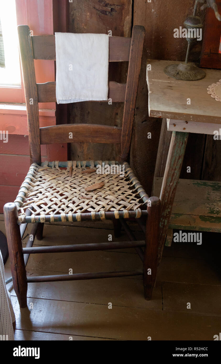 Antique wood chair with rustic cane woven seat next to old rustic wooden table.  Interior of old Texan home, Chestnut Square, McKinney Texas. Stock Photo