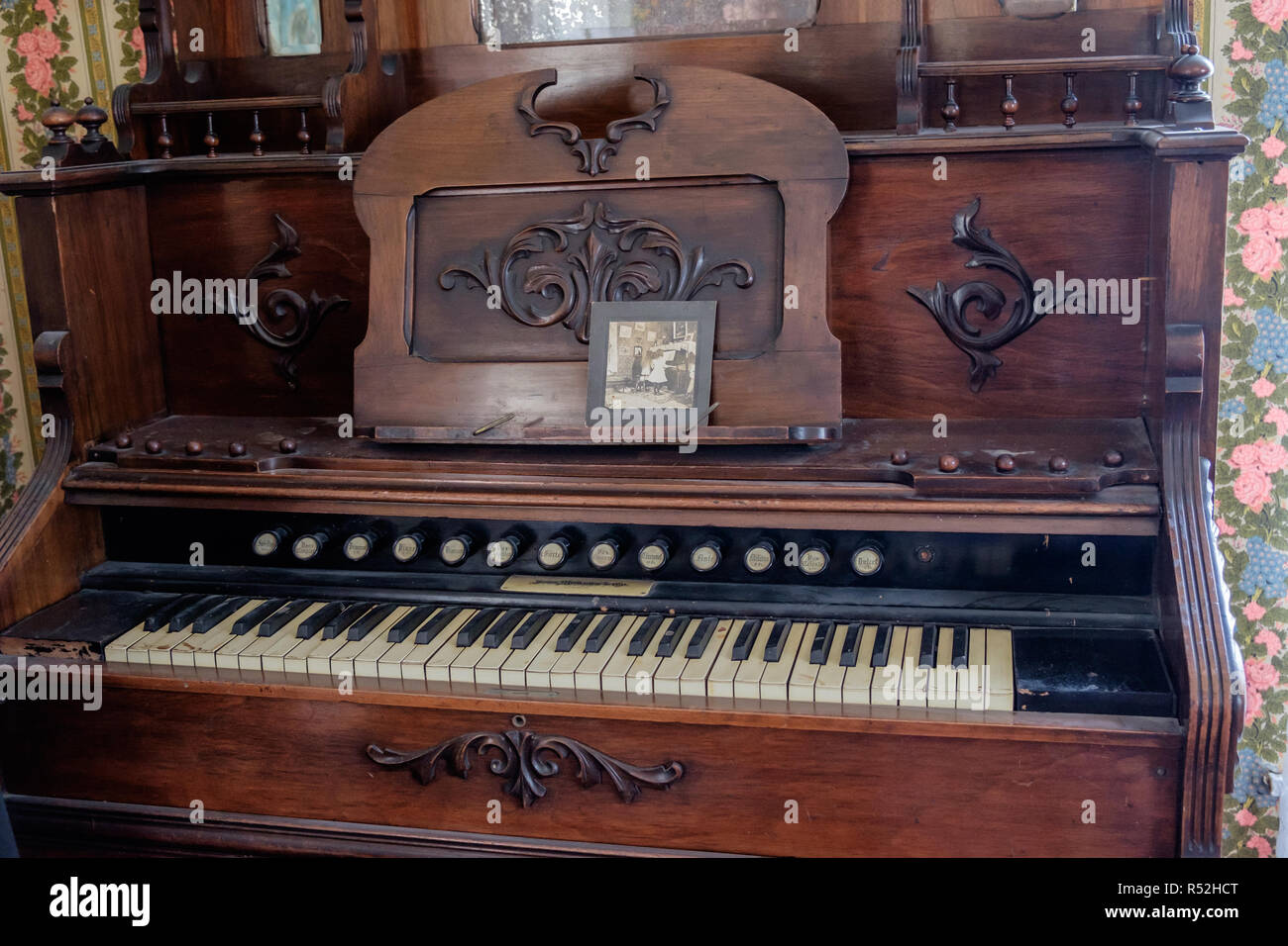 Antique  pump organ with sound buttons and piano keyboard. Old framed photo & vintage floral wall paper. Interior of Historic Texan home, McKinney. - Stock Image