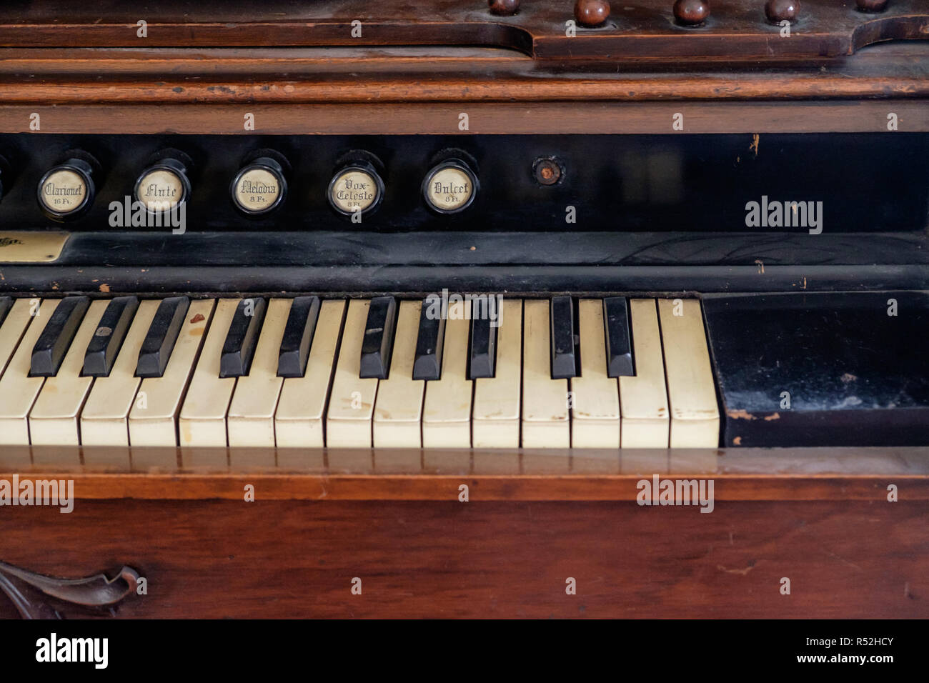 Close up of antique pump organ with sound buttons and piano keyboard. Interior of Texan home, Chestnut Square Historic Village, McKinney, Texas. - Stock Image
