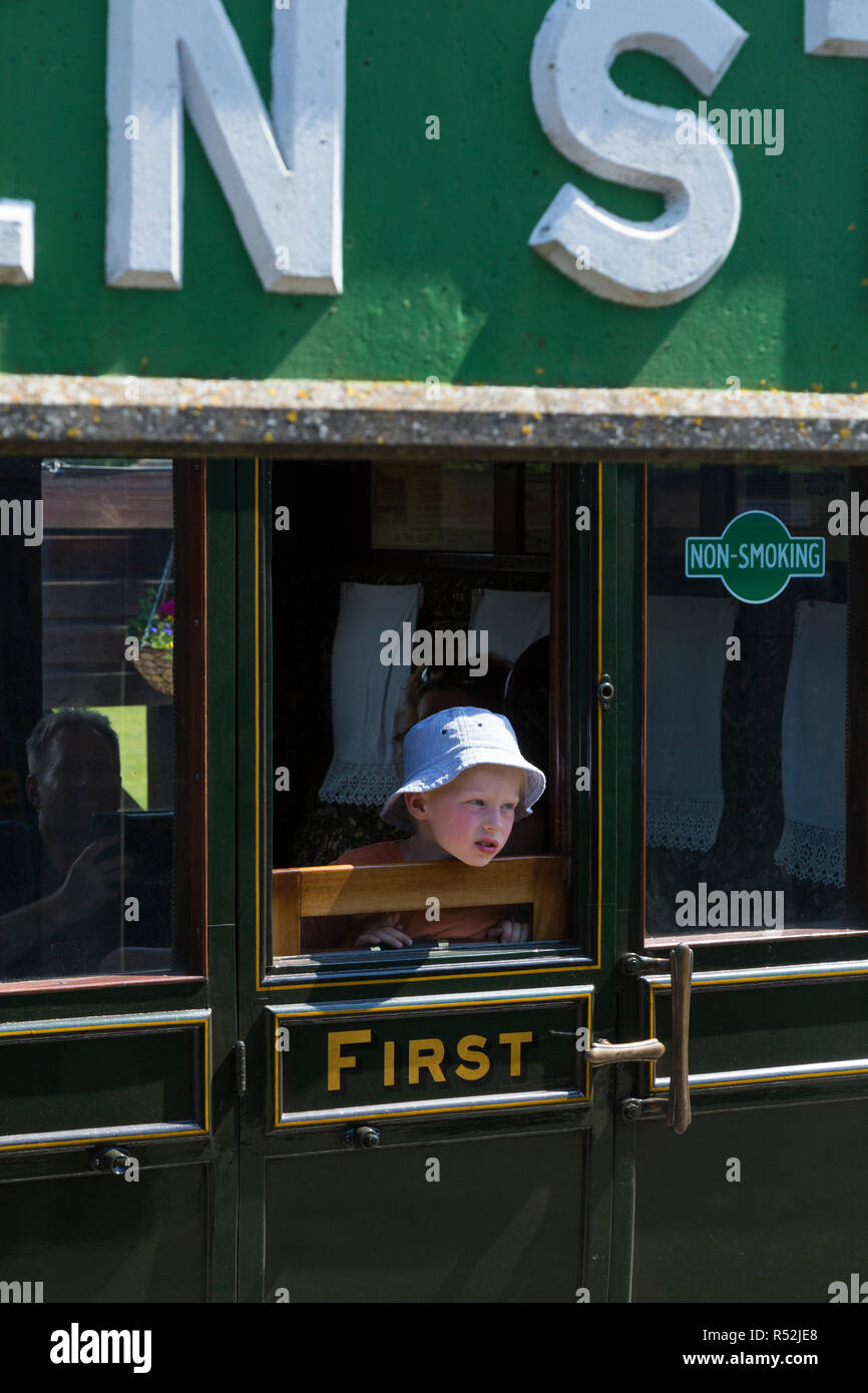 Child passenger / passengers aboard First / 1st class train carriage on the historic Isle of Wight steam Railway line, seen at Havenstreet Main Road, Haven Street station, Isle of Wight. England UK - Stock Image