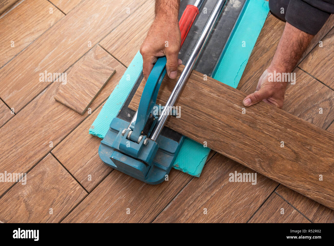 The man is cutting the floor tiles using a tile cutter
