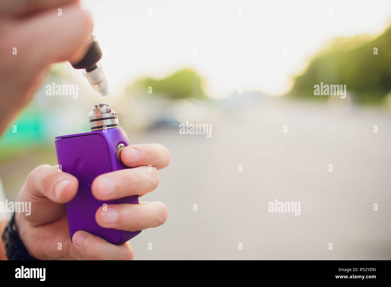 Rebuildable dripping atomizer or RDA for vaping or e-cigarette with coil and cotton stripes wetted with e-liquid, modern vape device for quit smoking, macro photo with selective focus - Stock Image