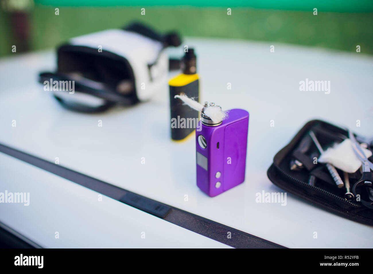 Rebuildable dripping atomizer or RDA for vaping or e-cigarette with Alien Clapton coil and cotton stripes wetted with e-liquid, modern vape device for quit smoking, macro photo with selective focus - Stock Image