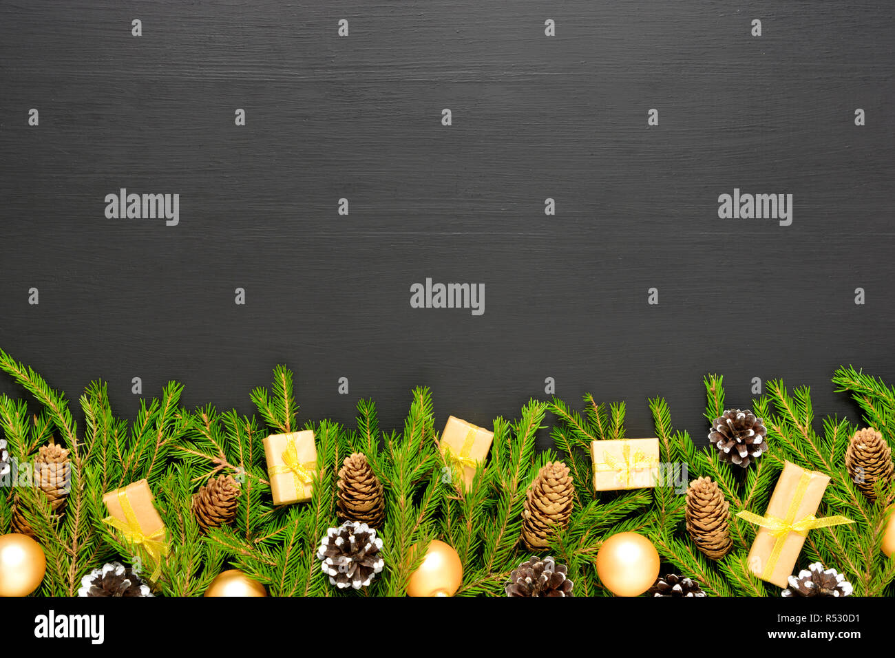 green fir branches with cones and decorates on black wooden desk christmas and new year