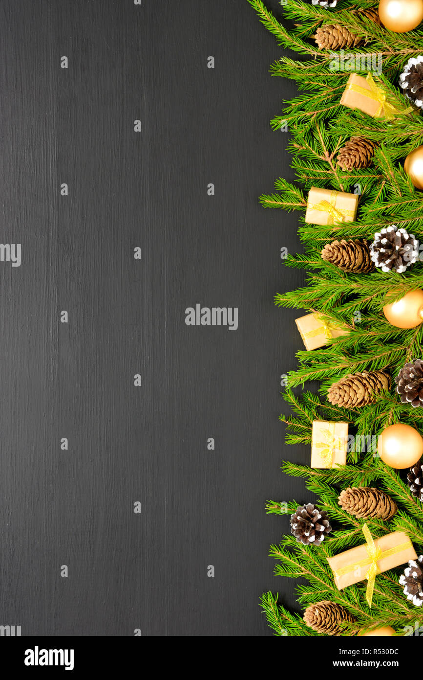 green fir branches with cones and decorates on black wooden desk christmas and new year border frame space for text