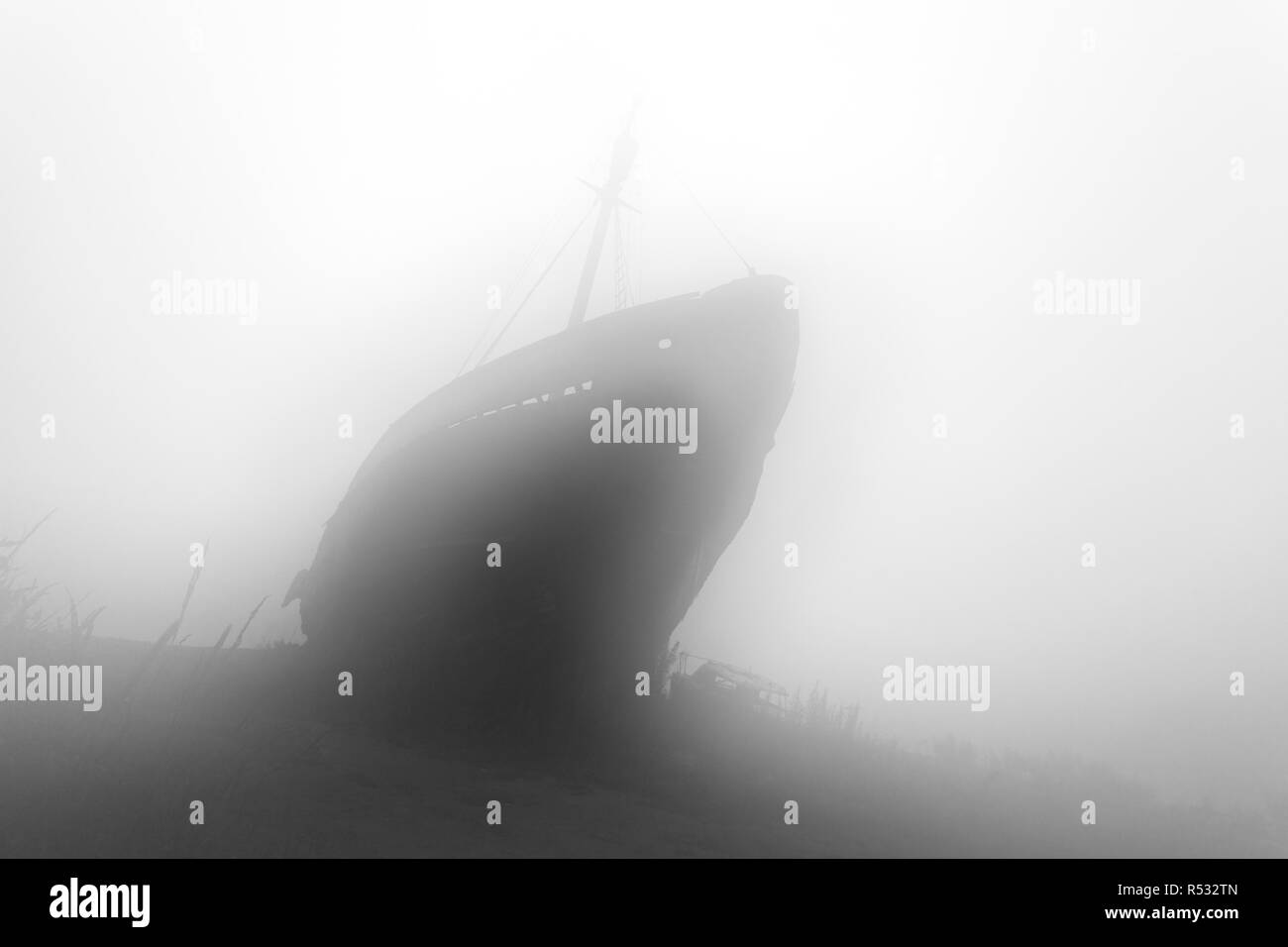 Old wrecked ship in the morning mist. Black and white image - Stock Image