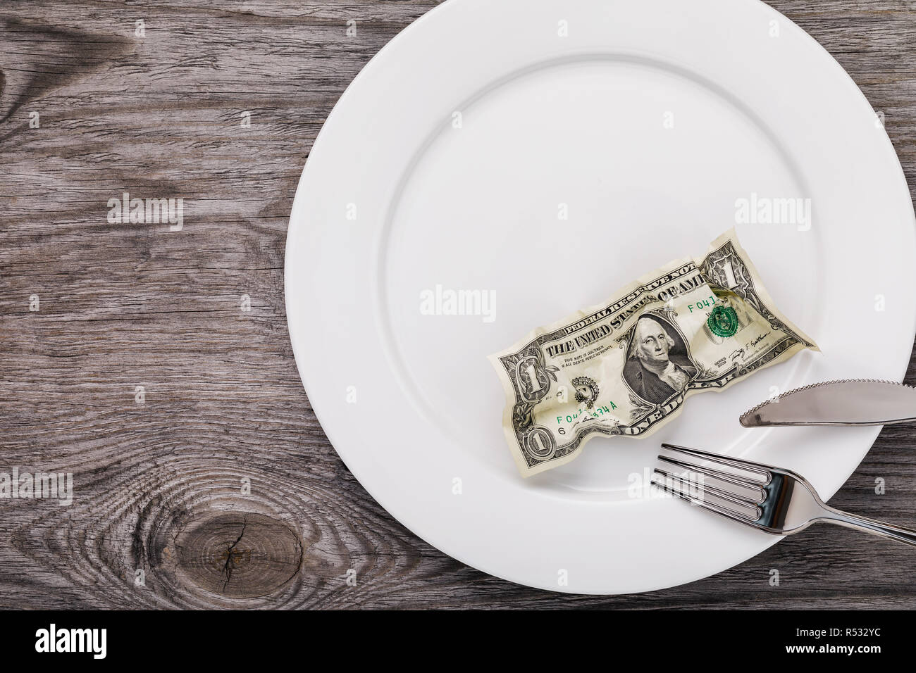 Top view on crumpled dollar in plate close-up with copy space - Stock Image