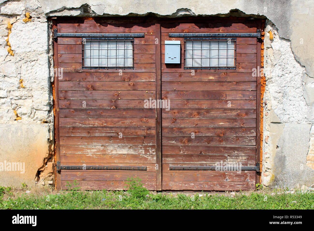 Garage doors made of small wooden boards with faded brown color and two small windows protected