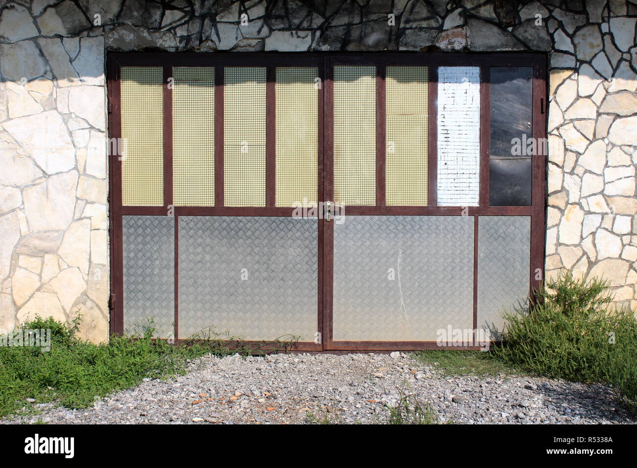 Homemade garage doors with strong metal frame, large sheet metal fillings and missing glass mounted on stone wall with gravel and uncut grass in front - Stock Image