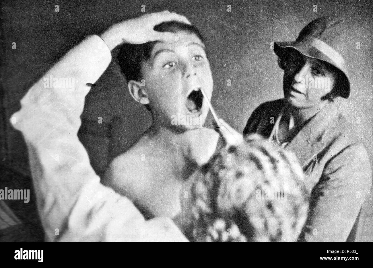 1934, Examining the teeth of a school pupil at one of the new school dental clinics. A boy is accompanied by his mother - Stock Image