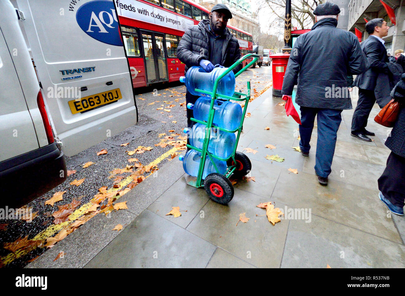 Man delivering water for water coolers and parked on a double yellow line, the Strand, London, England, UK. - Stock Image