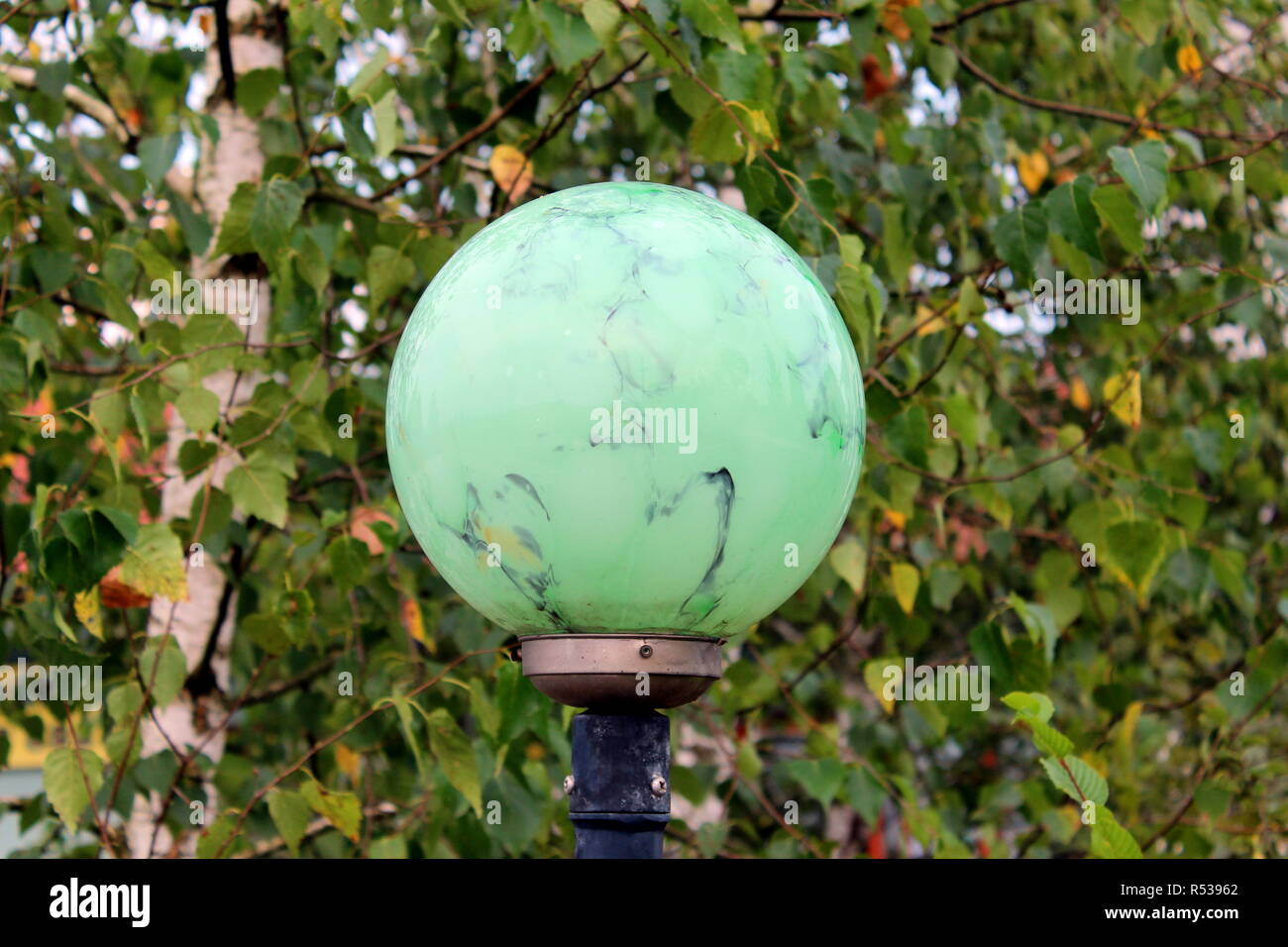 Light green marble like texture round street lamp mounted on metal pole on fresh green leaves background on warm summer day - Stock Image