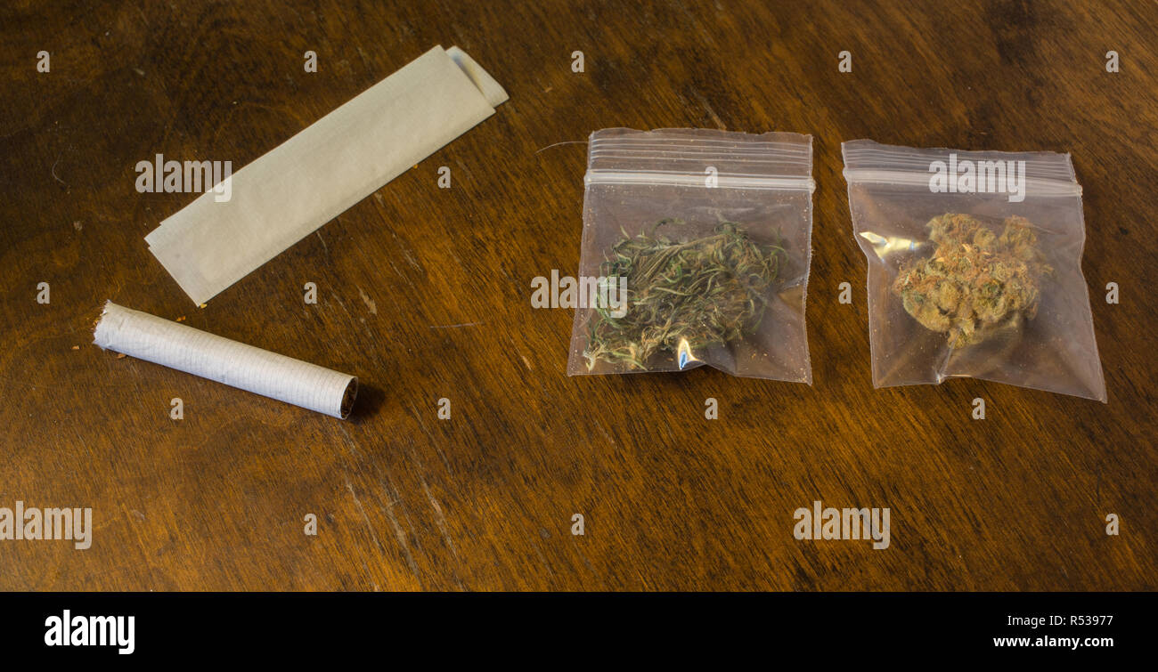 Two bags of cannabis and a cigarette and rolling paper. - Stock Image