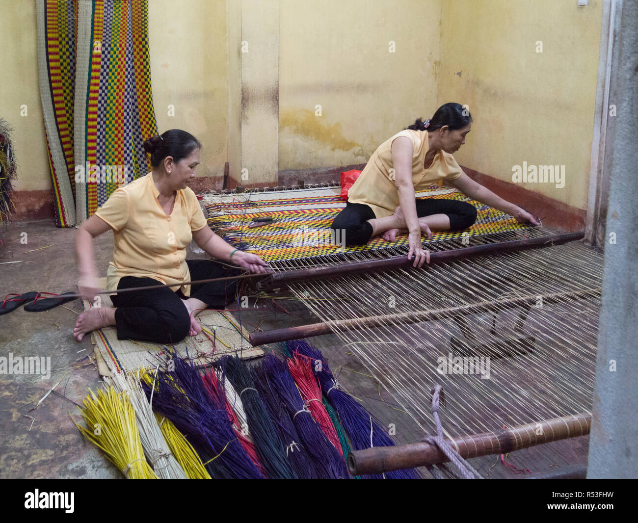 Two Vietnamese ladies sitting on the floor of silk sales shop weaving a colourful carpet Hoi An Vietnam Asia - Stock Image