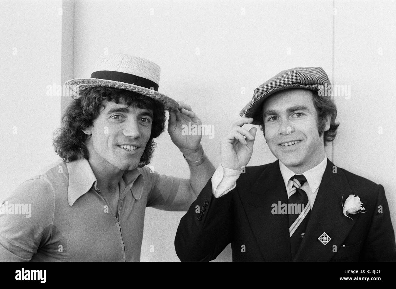 Kevin Keegan in a straw boater hat and Elton John in his own hat. They are pictured prior to leaving Luton Airport for Denmark with the England team. 18th September 1978. - Stock Image