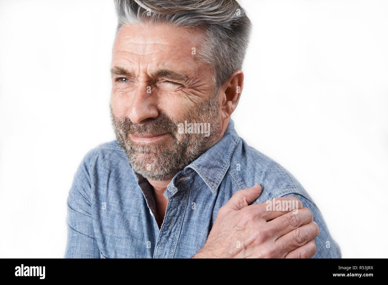 Studio Shot Of Man Suffering With Frozen Shoulder - Stock Image