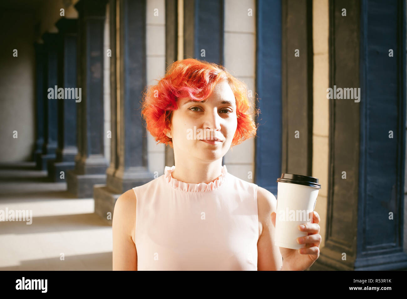 455ac152c3e23 girl in a pale pink dress with dyed red hair, a white backpack in hand,  drinks coffee from a cup, walking between light and shadow on the columns  sunny ...