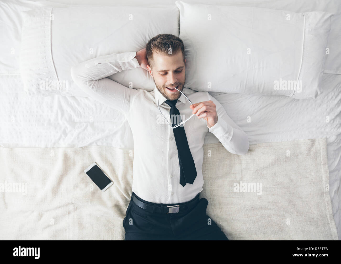 Top view. Handsome businessman with glasses lying on bed - Stock Image