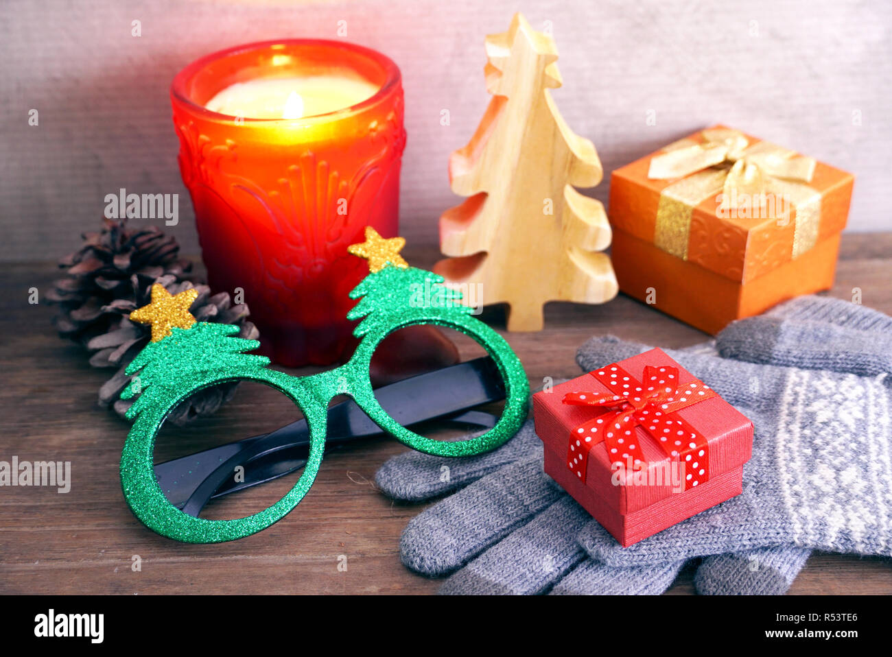 Red gift box on gray gloves with decorate objecton the table for chriatmas theme - Stock Image
