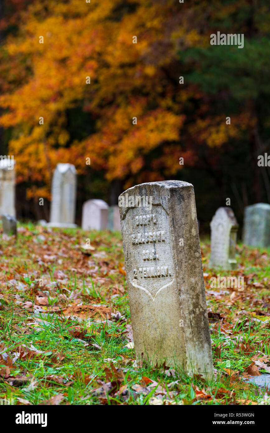 Vertical close-up shot of a Civil War tombstone from the side with other tombstones out of focus in the background in an old Smoky Mountains cemetery. - Stock Image