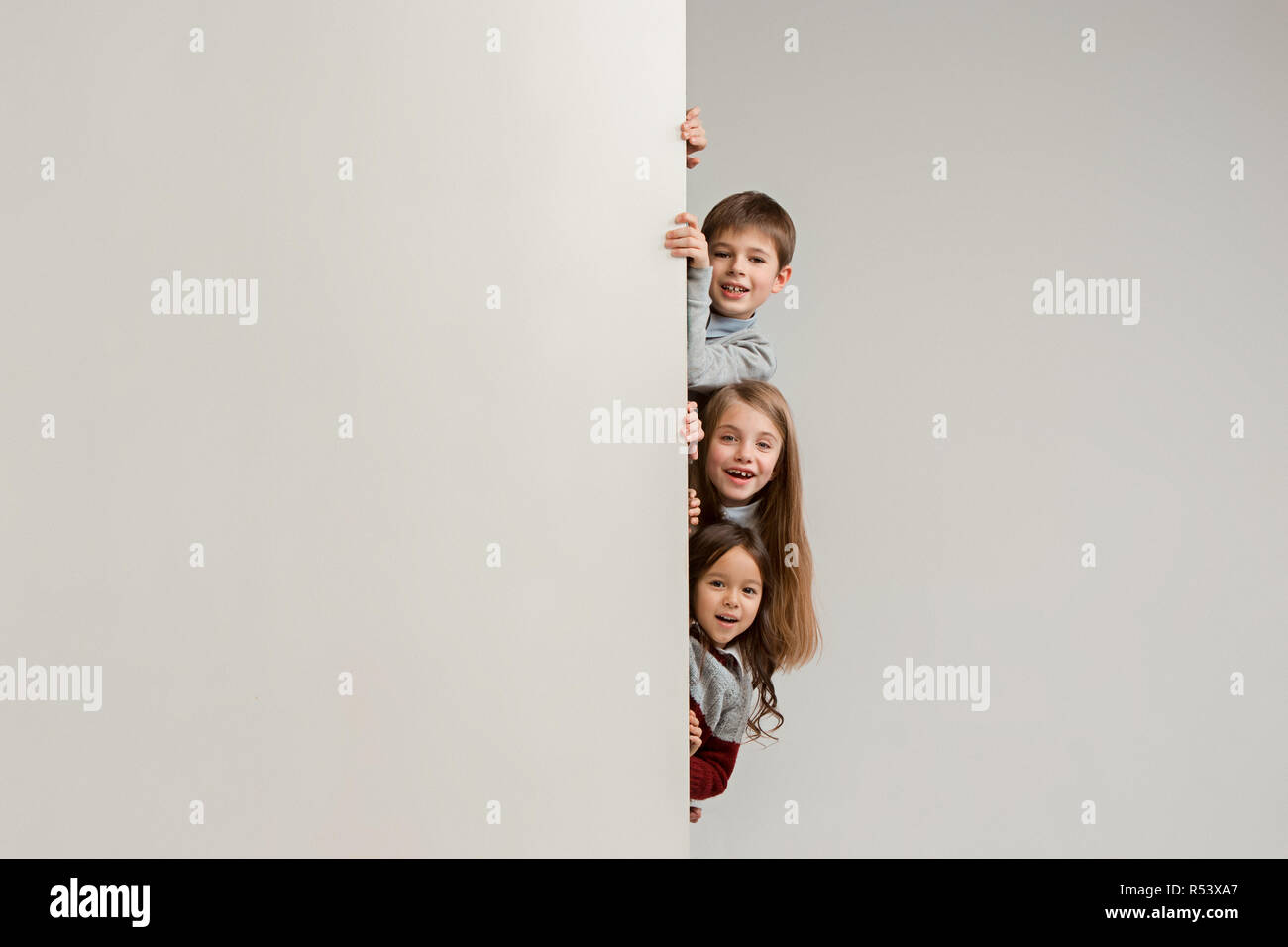 ab40f37d37 Banner with a surprised children peeking at the edge with copyspace. The  portrait of cute little kids boy and girls looking at camera against white  studio ...