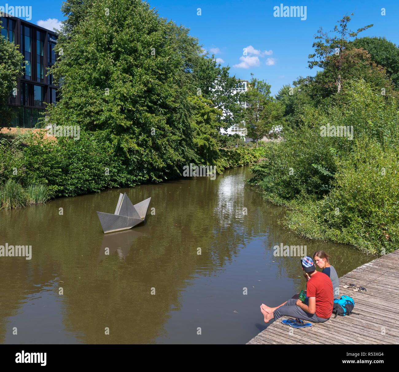 "Couple sitting on the waterfront with Erik Heide's sculpture ""Paper Boat"" behind, Hans Christian Andersen Garden, Odense, Funen, Denmark Stock Photo"