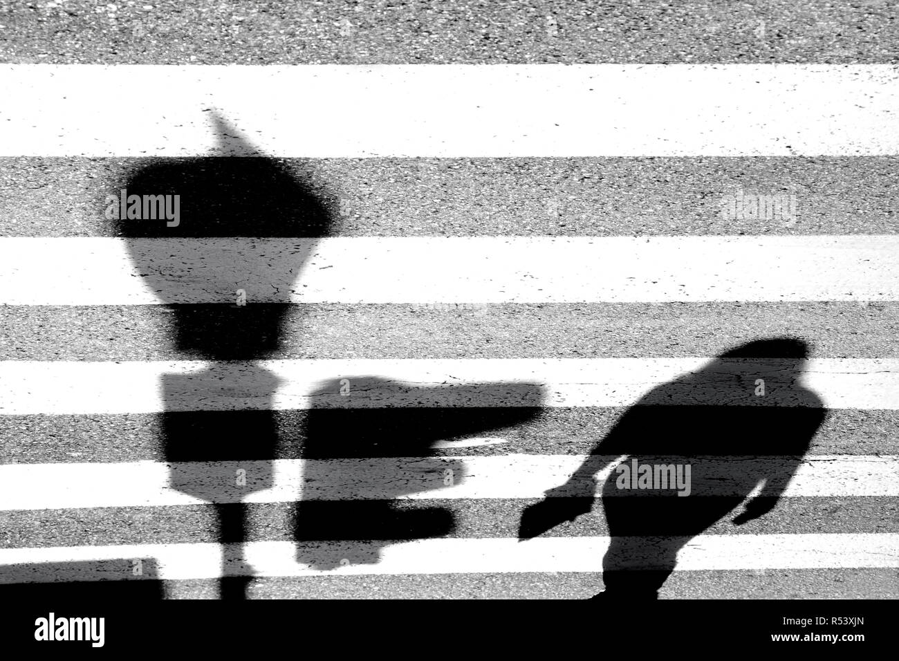 Blurry shadow of one pedestrian crossing the city street - Stock Image