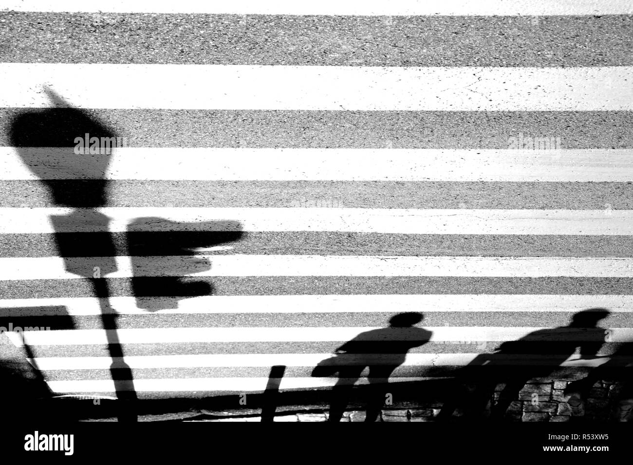 Blurry shadows of  pedestrians waiing at zebra sreet crossing with traffic light - Stock Image