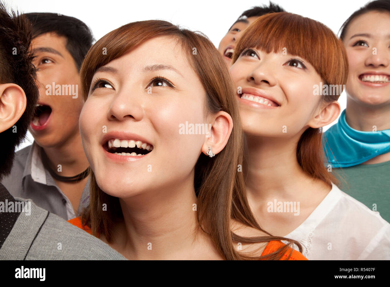 A group of young people looking up in excitement - Stock Image