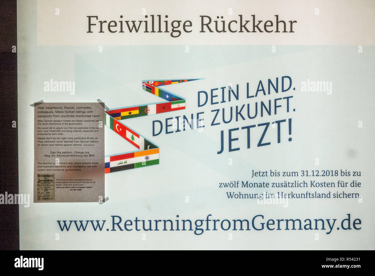 Berlin, Berlin, Germany. 24th Nov, 2018. An anti BMI pamphlet (L) informing about petition was taped to campaign poster by the German Ministry of the Interior, promotes the voluntary return of refugees to their home countries is seen at a metro underground station in Berlin, Germany, November 24, 2018. The Federal Office for Migration and Refugees Bondsman fuer Migration und Fluechtlinge or BAMF), initiated a campaign encouraging refugees to return to their source countries, through several advertising mediums, one of which as street posters. The campaign is drawing strong resistance and - Stock Image