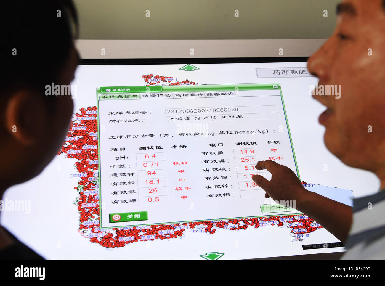 Beijing, China's Anhui Province. 2nd Apr, 2018. A technician explains the results of soil examination and the corresponding fertilizing plan to a farmer in Feixi County of Hefei, east China's Anhui Province, April 2, 2018. Credit: Liu Junxi/Xinhua/Alamy Live News - Stock Image