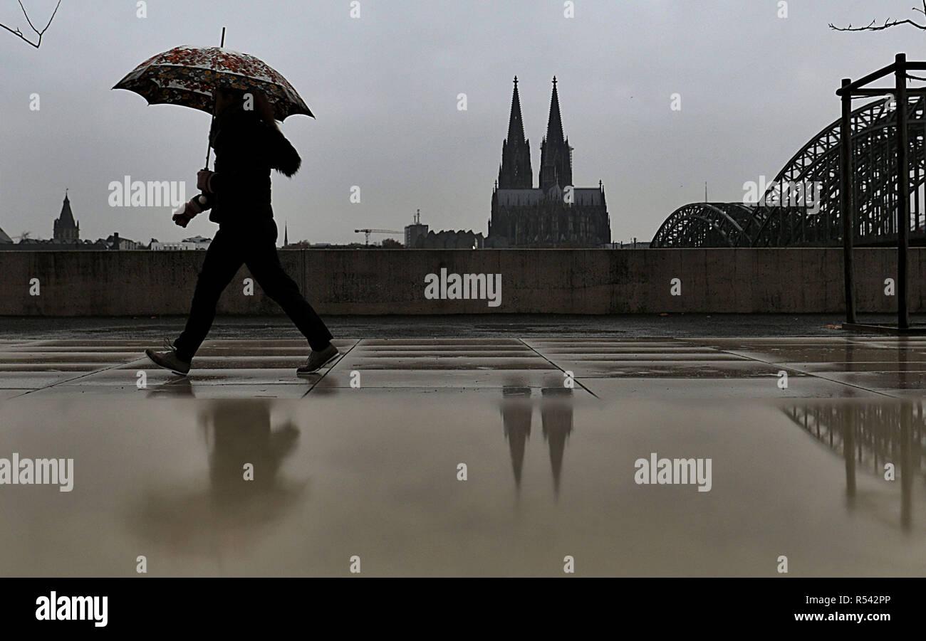 dpatop - 29 November 2018, North Rhine-Westphalia, Köln: A woman walks with her umbrella in the rain along the banks of the Rhine. - Alternative image detail - Photo: Oliver Berg/dpa Stock Photo