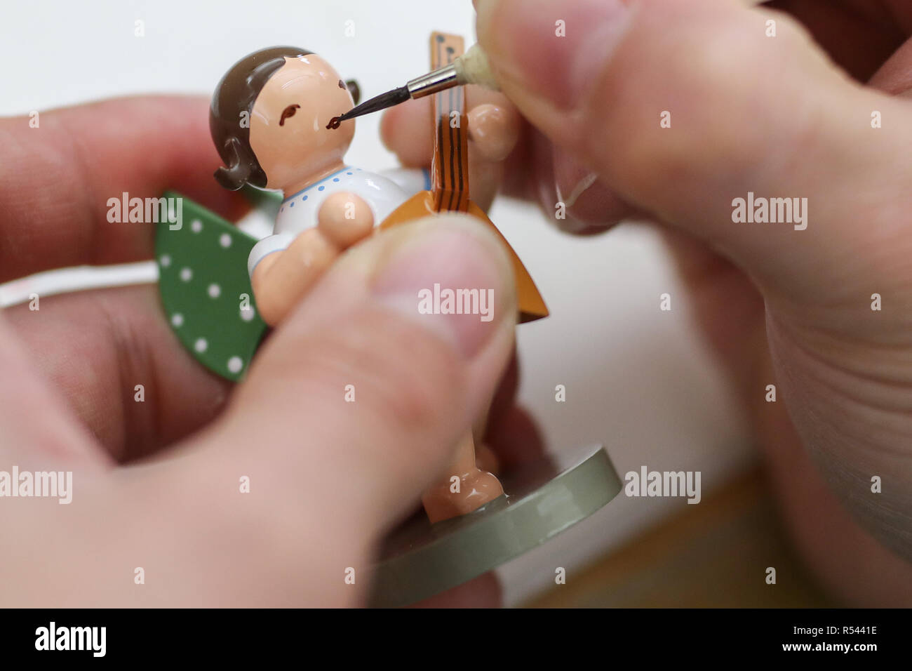 08 November 2018, Saxony, Grünhainichen: An employee of the Wendt&Kühn manufactory paints the face of an angel figure. Carving and the production of wooden toys are still an important branch of the economy in the Erzgebirge. The spectrum ranges from the classic two-man family business to large medium-sized companies. With almost 200 employees, Wendt&Kühn is one of the larger companies in the industry. Photo: Jan Woitas/dpa-Zentralbild/dpa - Stock Image