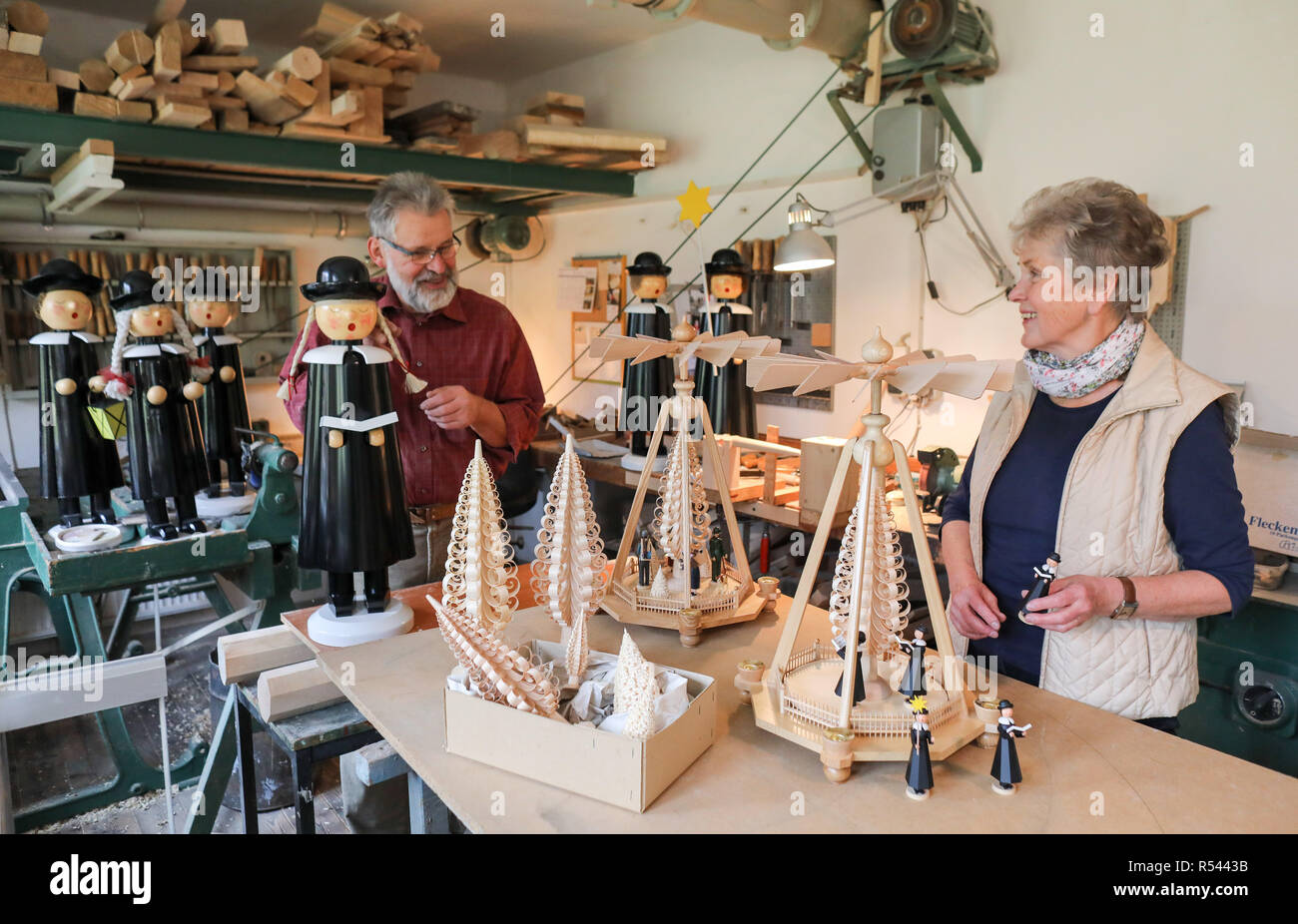 Einsiedel, Germany. 08th Nov, 2018. Barbara and Steffen Göthel are working on elephant singer figures and pyramids in the Erzgebirge arts and crafts enterprise Werner Glöß in Einsiedel. The small family business has been producing such decorative Christmas decorations for over 60 years. Carving and the production of wooden toys are still an important branch of the economy in the Erzgebirge. The spectrum ranges from such two-man family businesses to large medium-sized companies with several hundred employees. Credit: Jan Woitas/dpa-Zentralbild/dpa/Alamy Live News - Stock Image