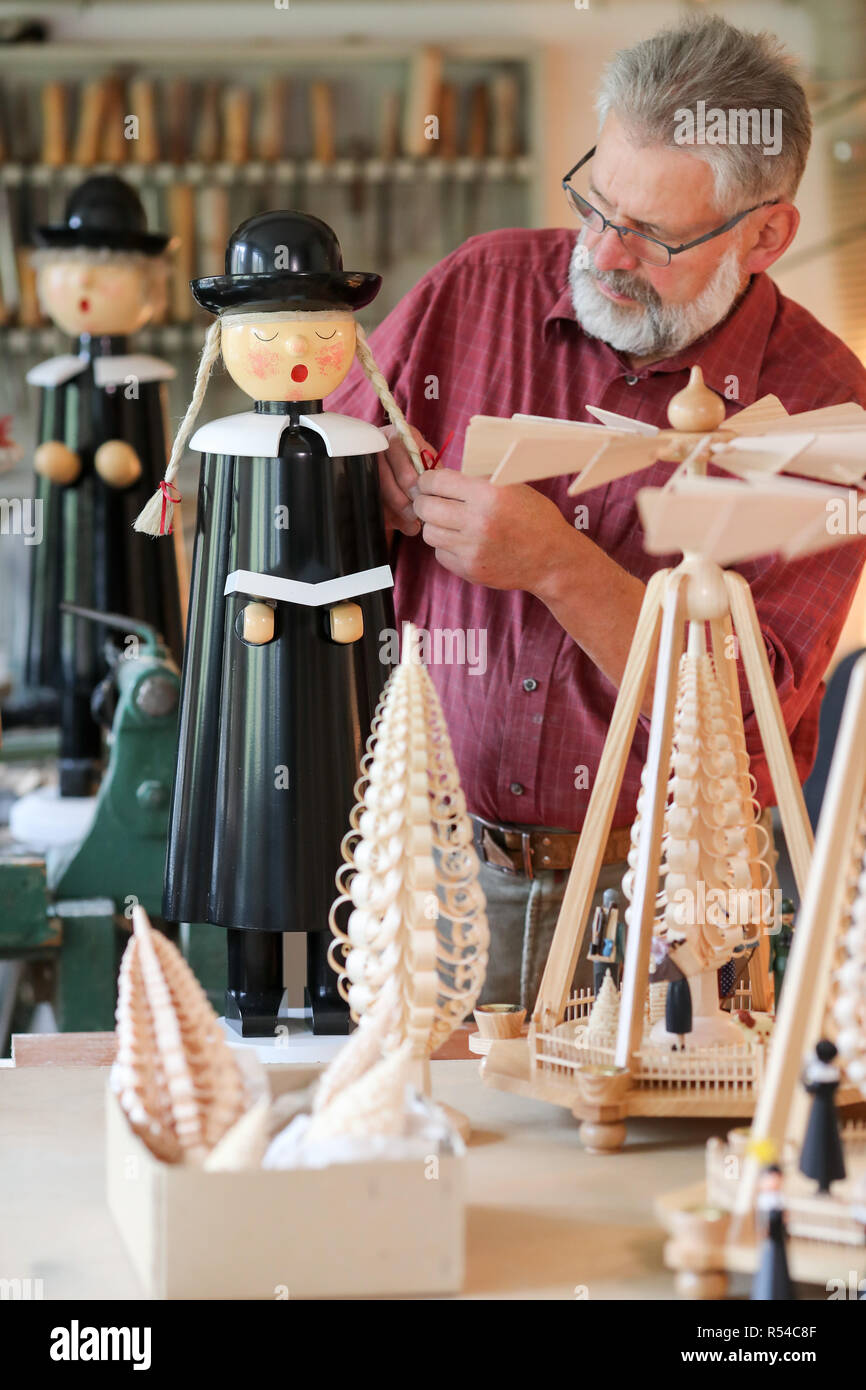 Einsiedel, Germany. 08th Nov, 2018. Steffen Göthel works on Kurrendesänger figures in his workshop in the Erzgebirge arts and crafts enterprise Werner Glöß in Einsiedel. The small family business has been producing such decorative Christmas decorations for over 60 years. Carving and the production of wooden toys are still an important branch of the economy in the Erzgebirge. The spectrum ranges from such two-man family businesses to large medium-sized companies with several hundred employees. Credit: Jan Woitas/dpa-Zentralbild/dpa/Alamy Live News - Stock Image